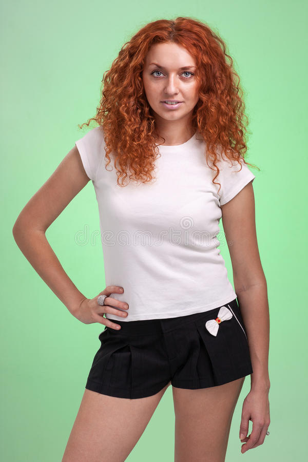 Red-haired woman in little shorts, isolated on green stock image