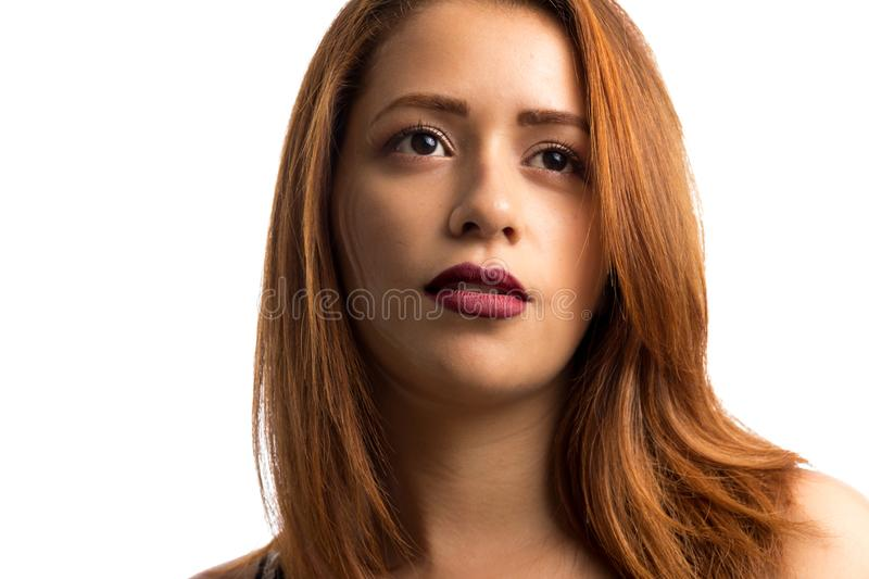 Red-haired woman looking away. Concept of aspirations, dreams and goals. Isolated on white background. Indoor portrait of red-haired woman looking away. Concept royalty free stock photo