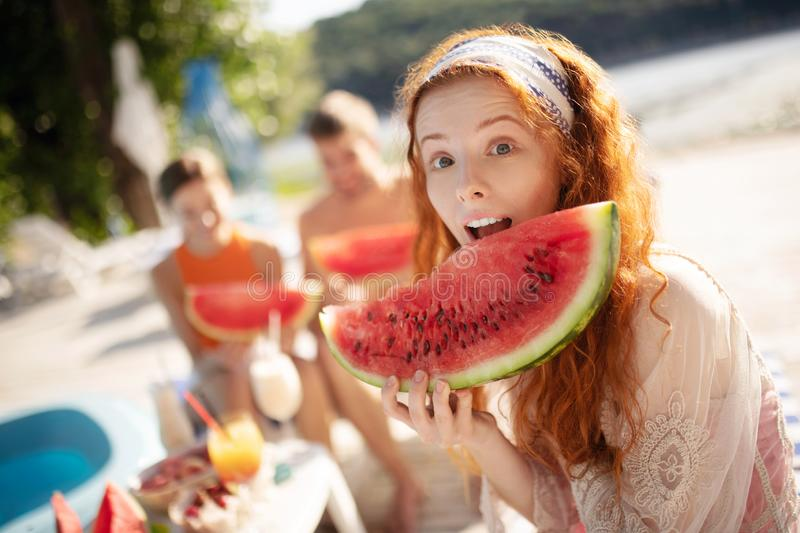Red-haired woman opening mouth while biting watermelon royalty free stock image
