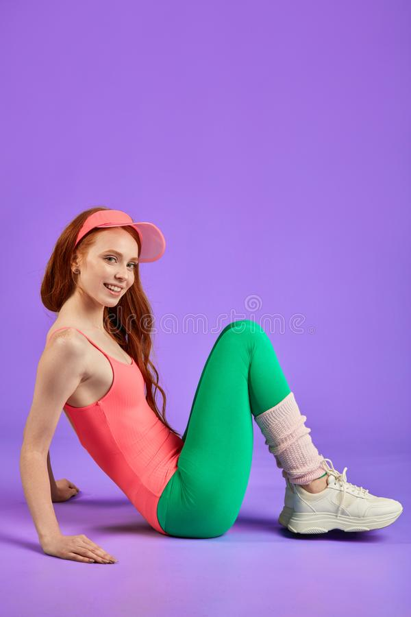 Relaxed young woman rests after active aerobics training. Red-haired woman rests after aerobics workout, sits on floor pulled up legs, drese in pink leotard stock images