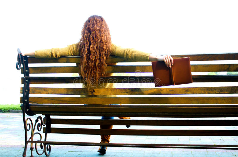 Red - haired woman sitting on bench with book. Red - haired woman sitting alone on bench with book royalty free stock images