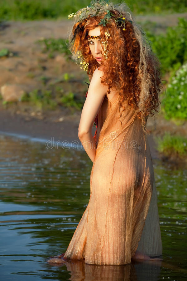 Red-haired woman in a transparent dress. royalty free stock photography