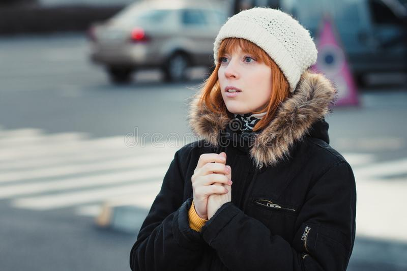 Red-haired woman wearing white knitted hat and dressed in warm hooded casual parka jacket outerwear, girl in the parking lot,. Pedestrian crossing and car in stock photo