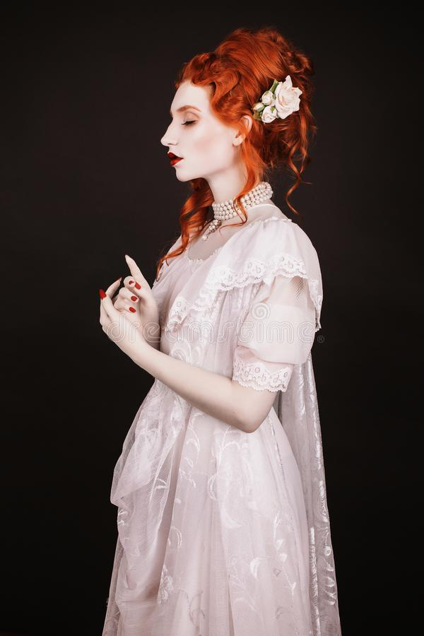 Red-haired woman in white dress with pale skin on a black background. Woman vampire in the gothic style in the Halloween look royalty free stock photos