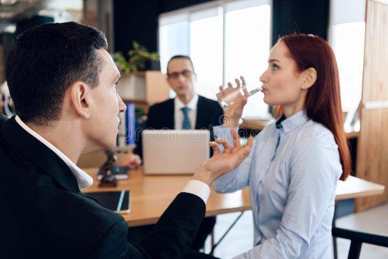 Red-haired woman is drinking glass of water, sitting next to adult man in divorce lawyer`s office. stock photos