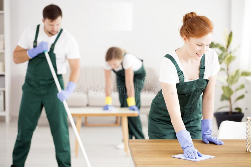 Red-haired woman cleaning table. Red-haired women in green overalls and with blue gloves cleaning the table royalty free stock photography
