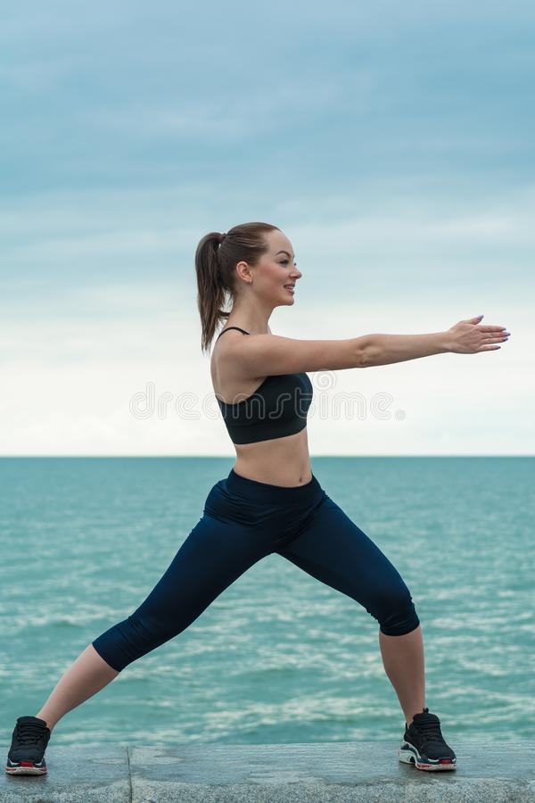 Red-haired, young, athletic, beautiful girl engaged in gymnastics, run in the open air. Performs sports exercises for the. Stretching, warm-up. Workout outdoors royalty free stock image