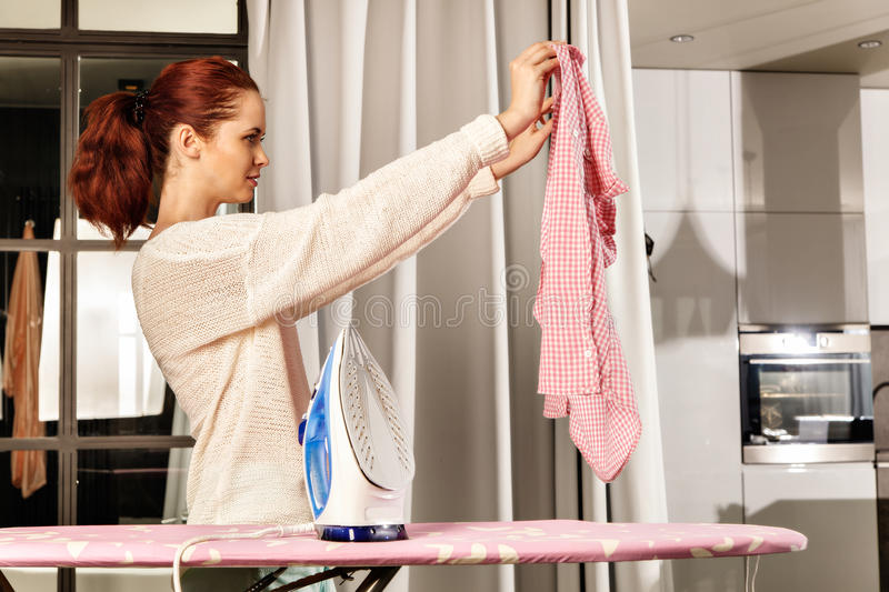 Red-haired young beautiful woman ironing clothes royalty free stock photography