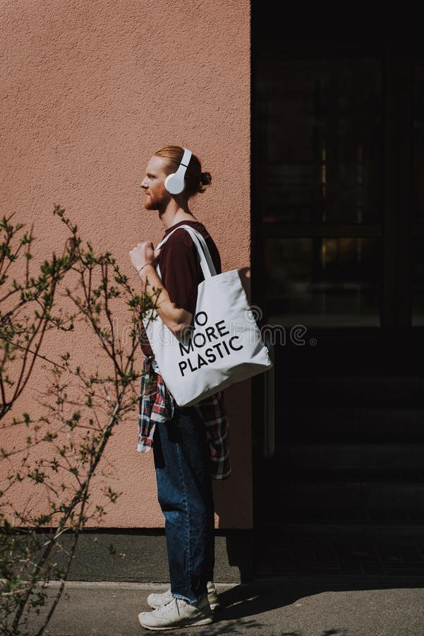 Red haired young hipster man going to walk. Urban lifestyle and safe environment. Full length side on portrait of young red haired hipster guy with headphones on royalty free stock images