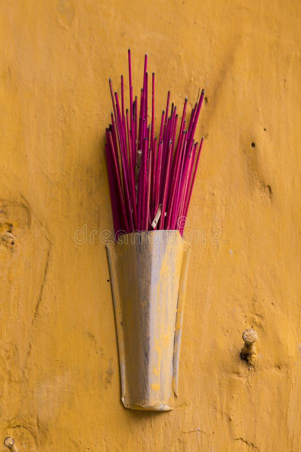 Red half-consumed incense sticks in small holder royalty free stock photo