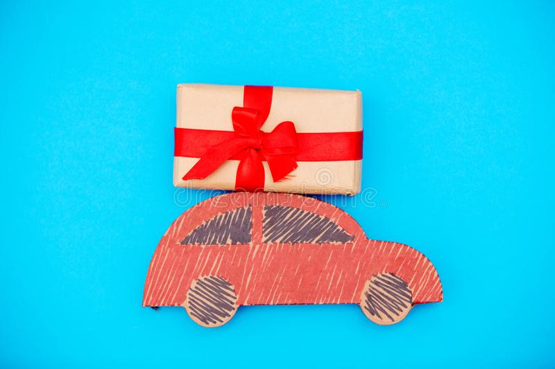 Red handmade car delivery with Christmas gift box. On blue background royalty free stock photography