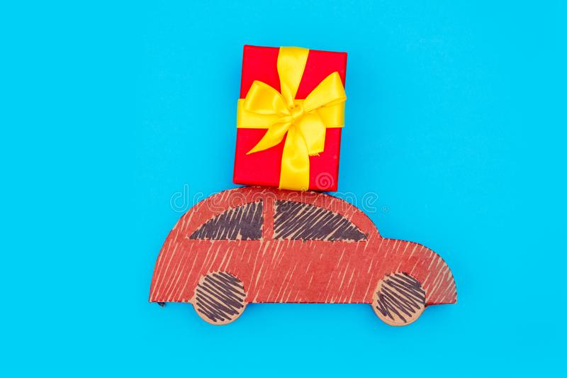 Red handmade car delivery with Christmas gift box. On blue background royalty free stock photos