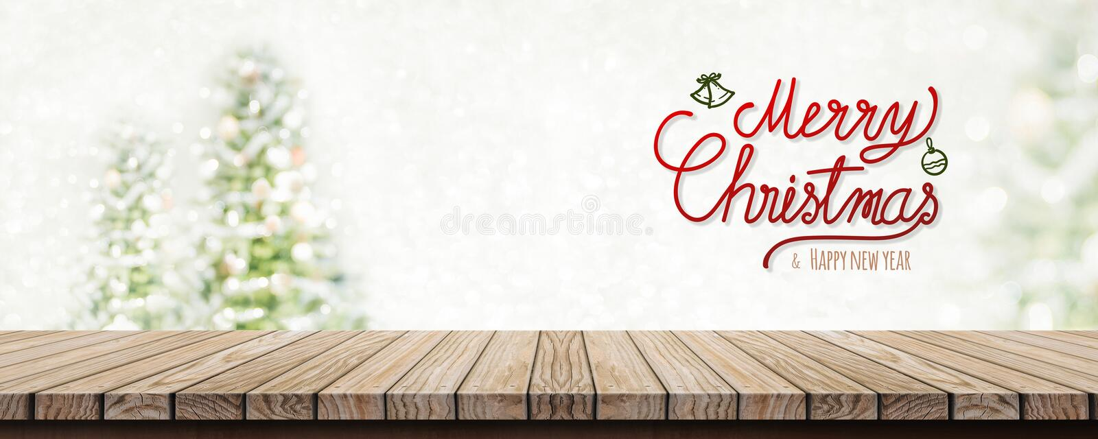 Red handwriting merry christmas and happy new year over wood tab. Le top with abstract blur christmas tree and snow fall background with bokeh light.Mock up stock images