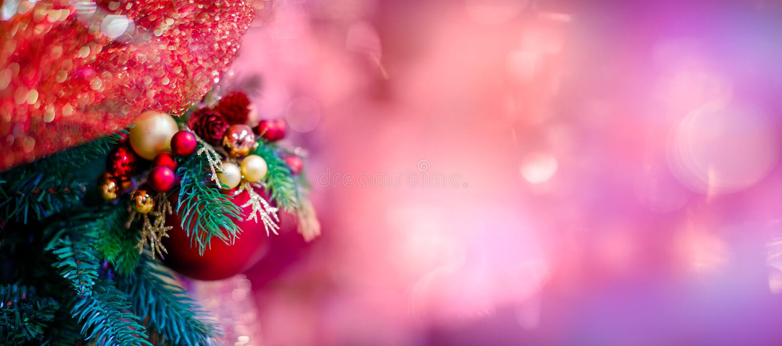 Red hanging ball ornament for Christmas tree. Shiny light flare Merry Xmas decoration background with copy space for. Text message or logo. Social or digital stock image