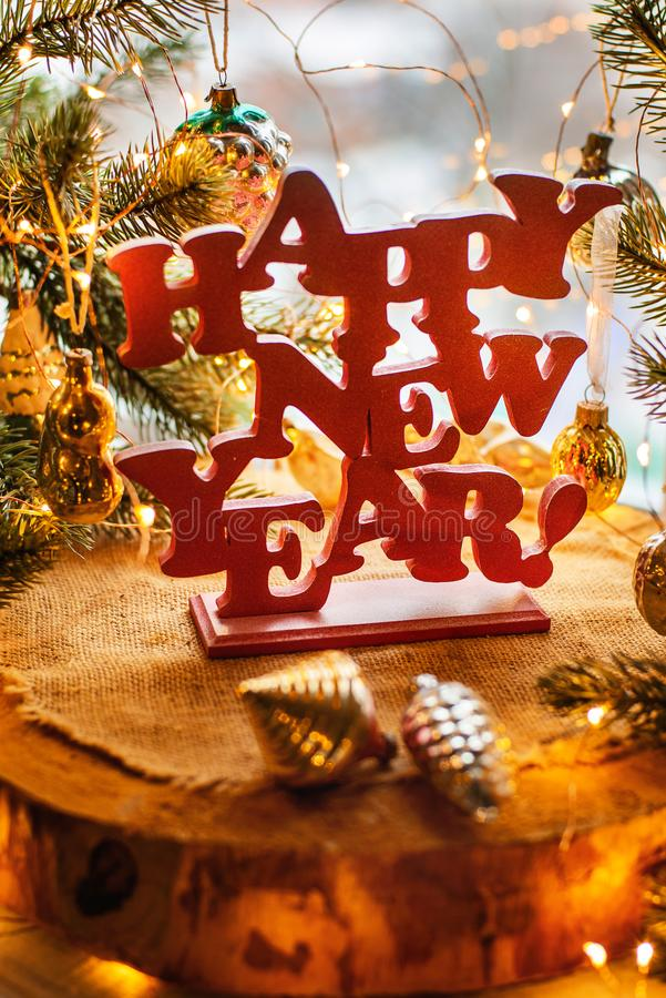 Happy new year. Red happy new year sign on a wooden background with fur tree, lights and vitntage Soviet toys royalty free stock photos