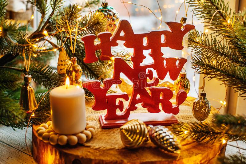 Happy new year. Red happy new year sign on a wooden background with fur tree, lights and vitntage Soviet toys stock photo