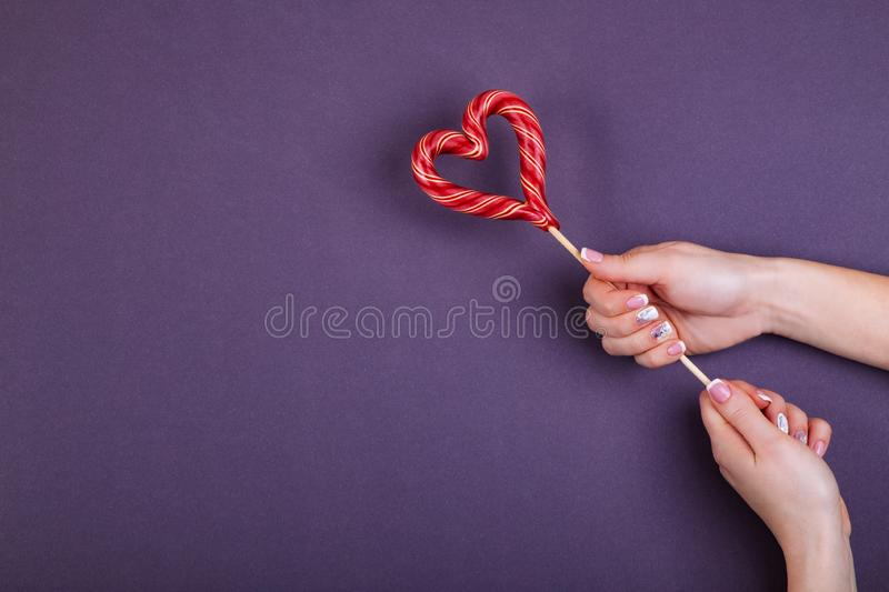 Lollypop on a stick in hand. Red hart shaped lollypop on a stick in female hands. Concept of stylish french manicure. Flat lay style royalty free stock image