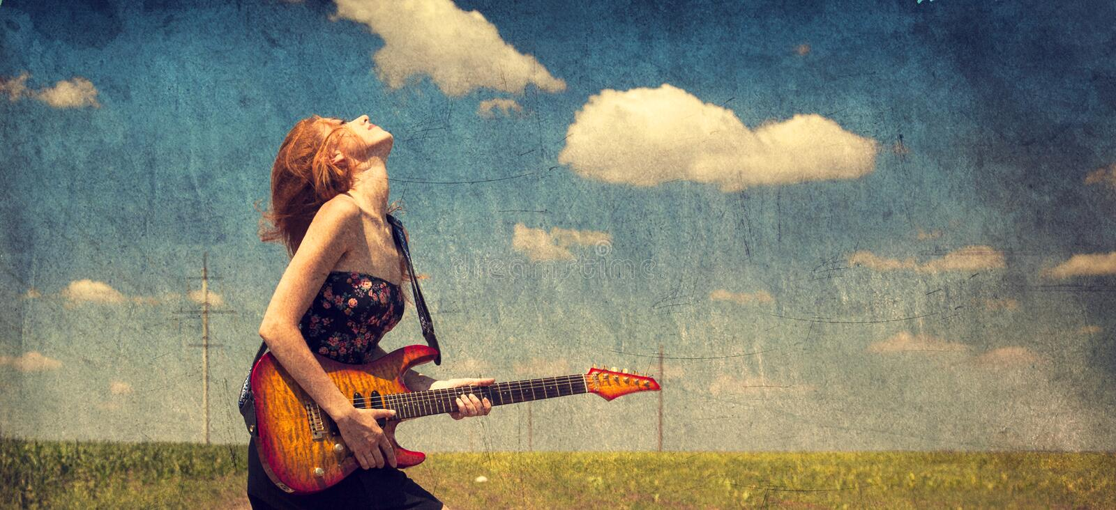 Red-head girl with guitar. Photo in old image style. royalty free stock images