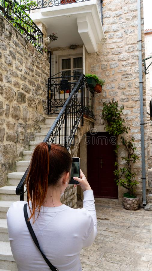 Red head girl taking a picture in the stone narrow streets of a town in the adriatic coast. Woman making photo with smart phone to. A house in Budva royalty free stock photos