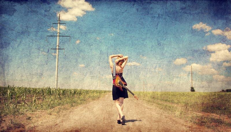Red-head meisje met gitaar. Foto in oude beeldstijl. royalty-vrije stock afbeeldingen