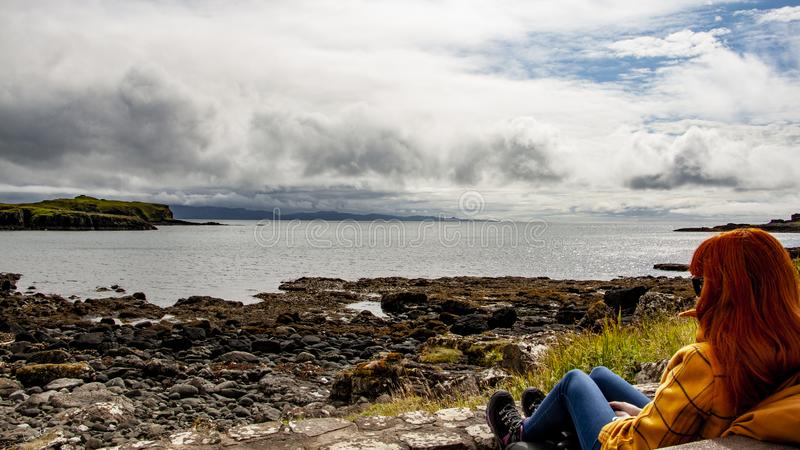 Red head women viewing the sea in Scotland royalty free stock photography