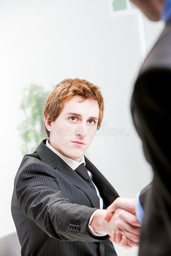Red headed businessman shaking hands royalty free stock image