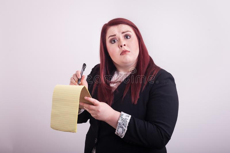 Red headed female wearing business suit taking notes on yellow notepad stock photo