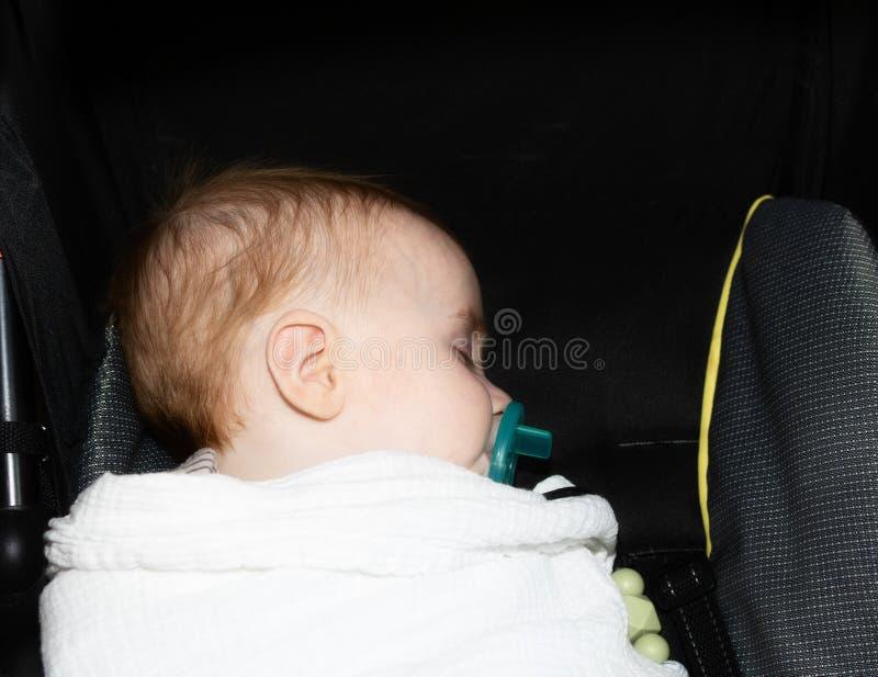 Red-headed Slaap van de Babyjongen in Vervoer met een Fopspeen wordt verpakt die stock fotografie