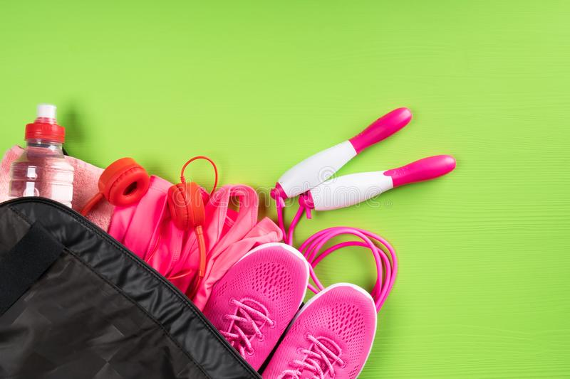 Red headphones in a sports bag with things on the corner of a green background, blank space for an inscription stock photos