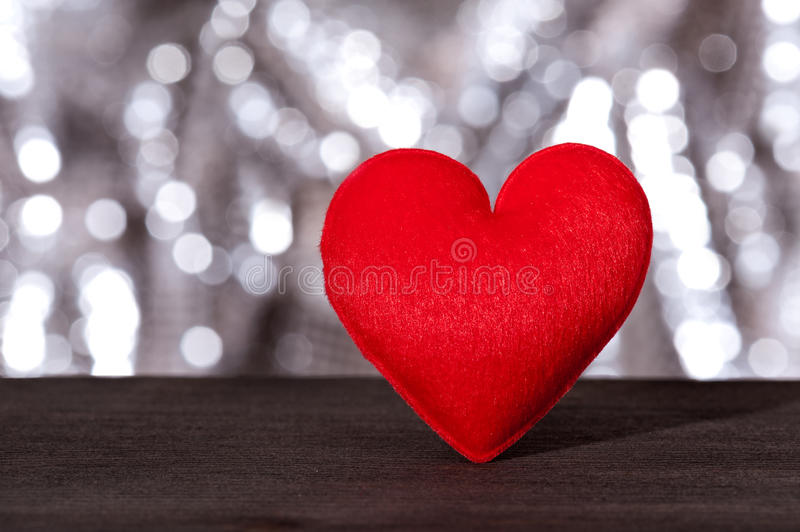 Red heart. In front of a silver sparkling background stock photo