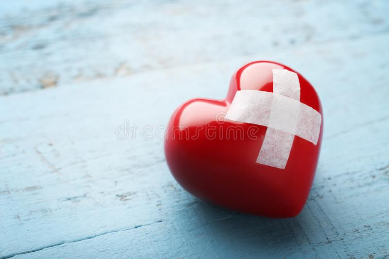 Red heart with adhesive bandage stock photography
