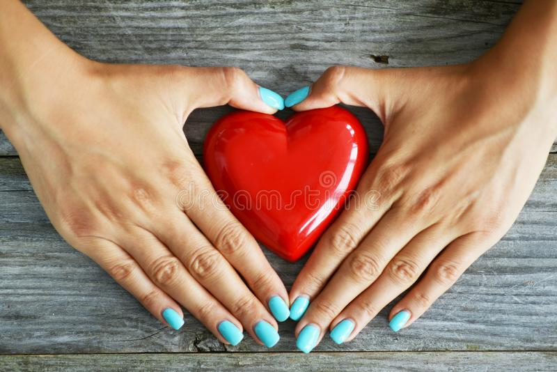 Red heart as love symbol in woman hand on rustic wooden background stock photo