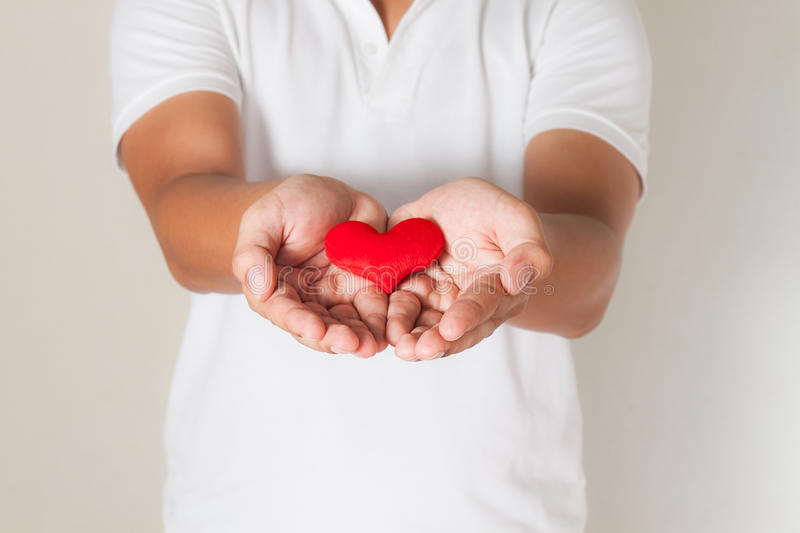 red heart in asian man hands,health- medicine and charity concept stock image
