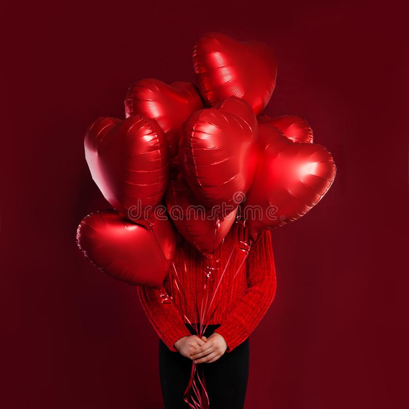 Red heart balloons in female hands on red background. Love, valentines people and Valentine`s day concept royalty free stock images