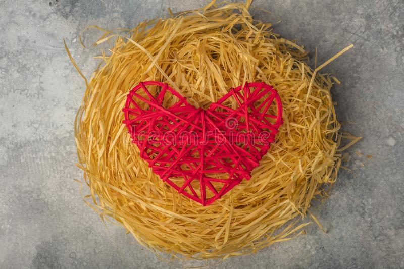 Red heart in a bird`s nest. The theme of love, family and the day of the holy valentine. View from above. royalty free stock photos
