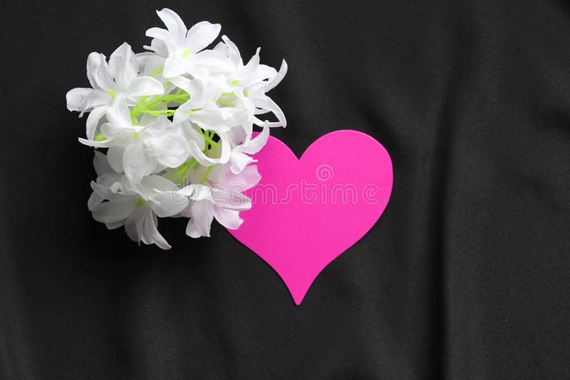 Red heart on a black background and white flowers. Symbol of love. Background - black satin material. Template for postcards stock images