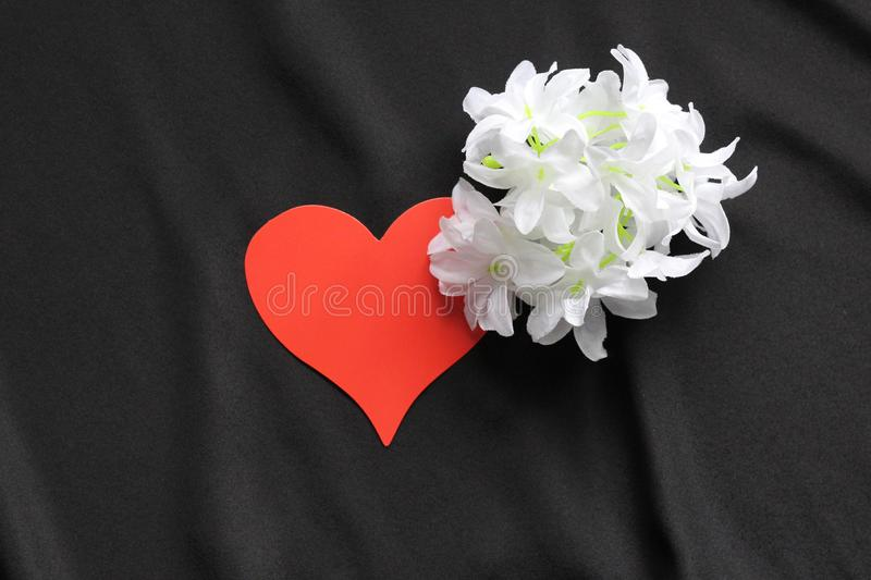 Red heart on a black background and white flowers. Symbol of love. Background - black satin material. Template for postcards royalty free stock images