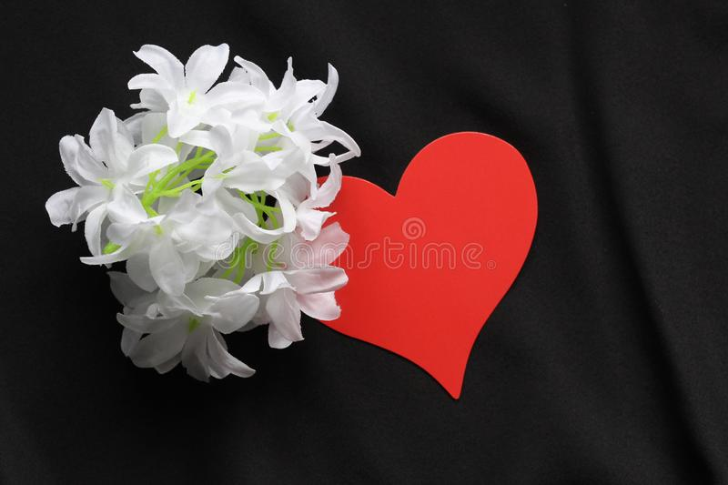 Red heart on a black background and white flowers. Symbol of love. Background - black satin material. Template for postcards stock photos