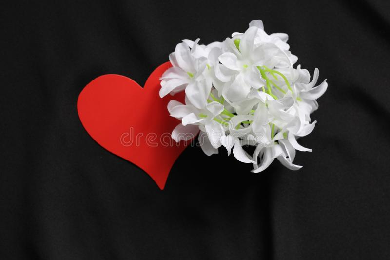 Red heart on a black background and white flowers. Symbol of love. Background - black satin material. Template for postcards royalty free stock photo