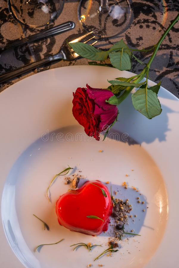 Red heart cake served on white plate on valentines day with roses, romantic evening and gift.  stock photo