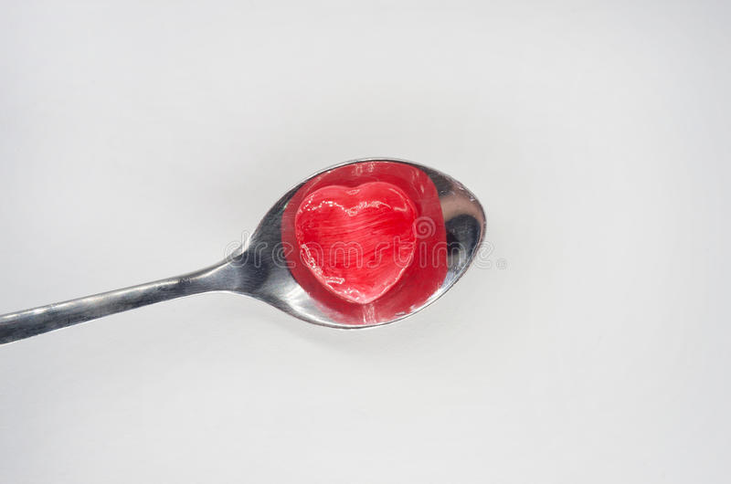 Red heart candy on spoon stock image