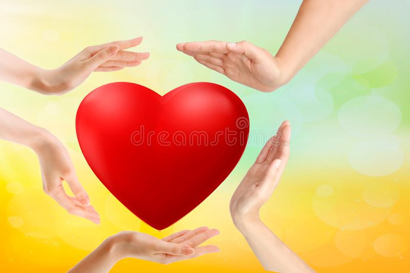 Red heart in child and female hands over wooden background, copy space. Kindness, family, love and charity concept, hand made stock photo