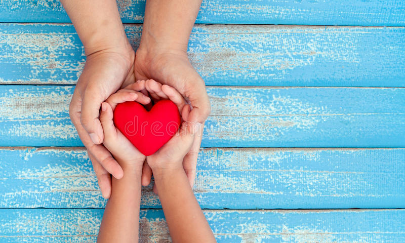 Red heart in child kid and mother hands on old blue wooden table royalty free stock images