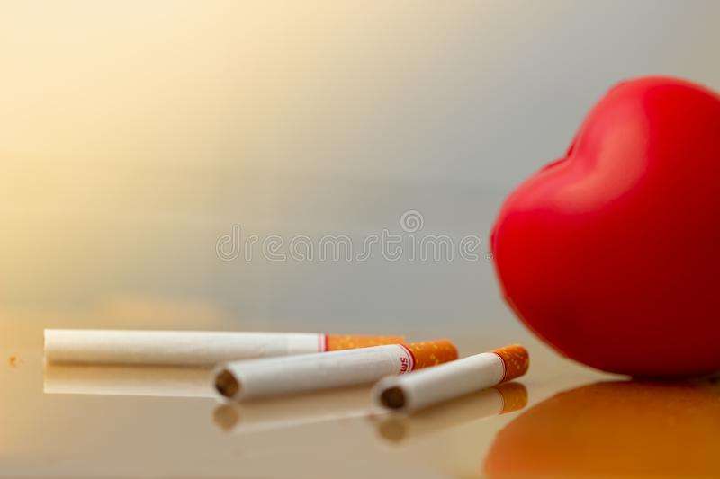 Red heart and cigarettes. Smoking cigarette destroying health. heart disease. royalty free stock images