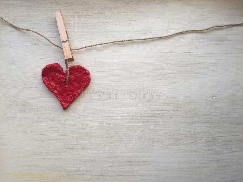Red heart in the clothesline on a white wooden background royalty free stock photos