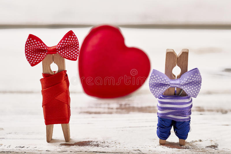 Red heart and clothespin couple. Heart on wooden background. Couple personalization by clothespins stock photography