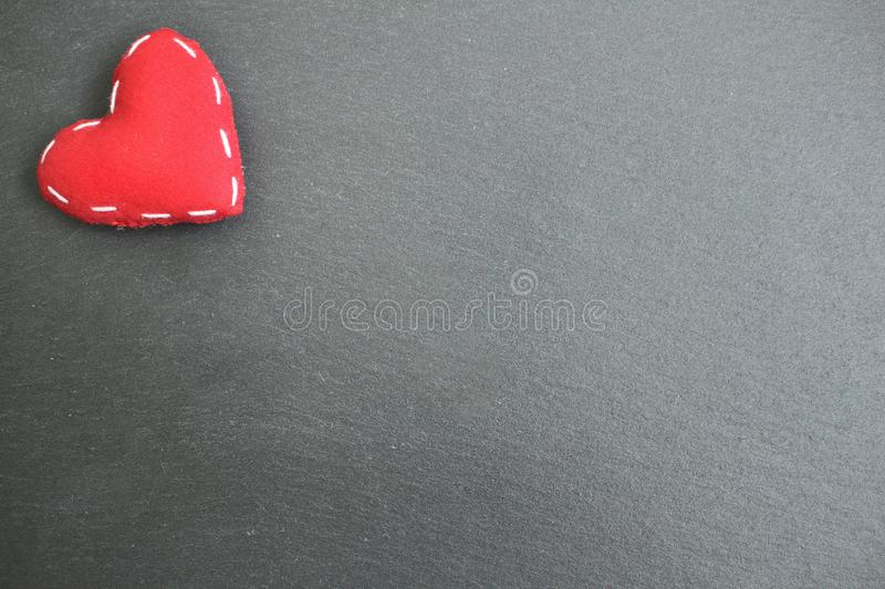 A red heart in corner on black slate background for background message royalty free stock images
