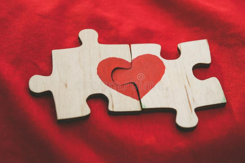Red heart is drawn on the pieces of the wooden puzzle lying next to each other on red background. Love concept. St. Valentine day stock photography