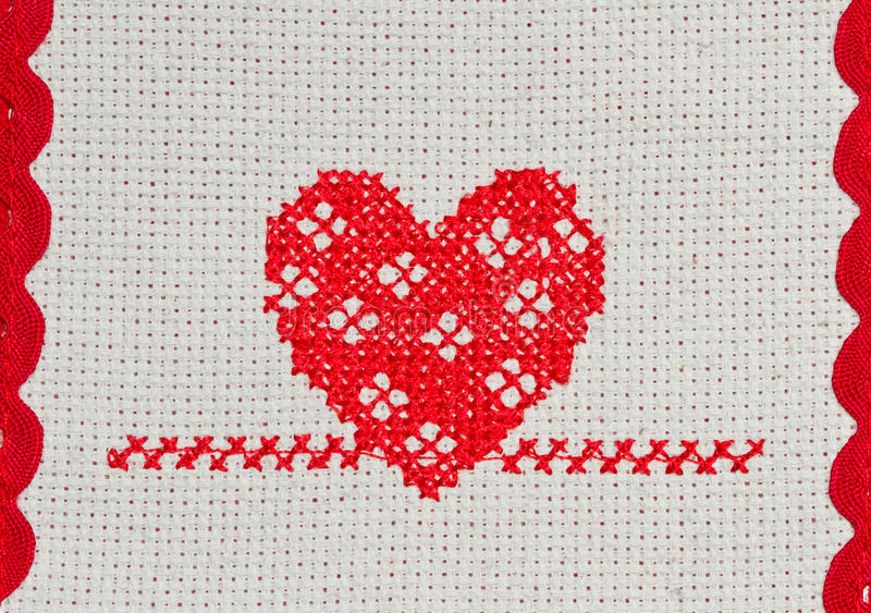 Red heart embroidered in cross stitch royalty free stock photography