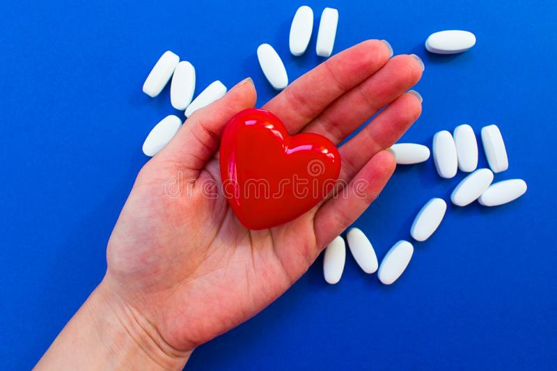 Red heart on the female palm on a blue background with white pills ... royalty free stock photo
